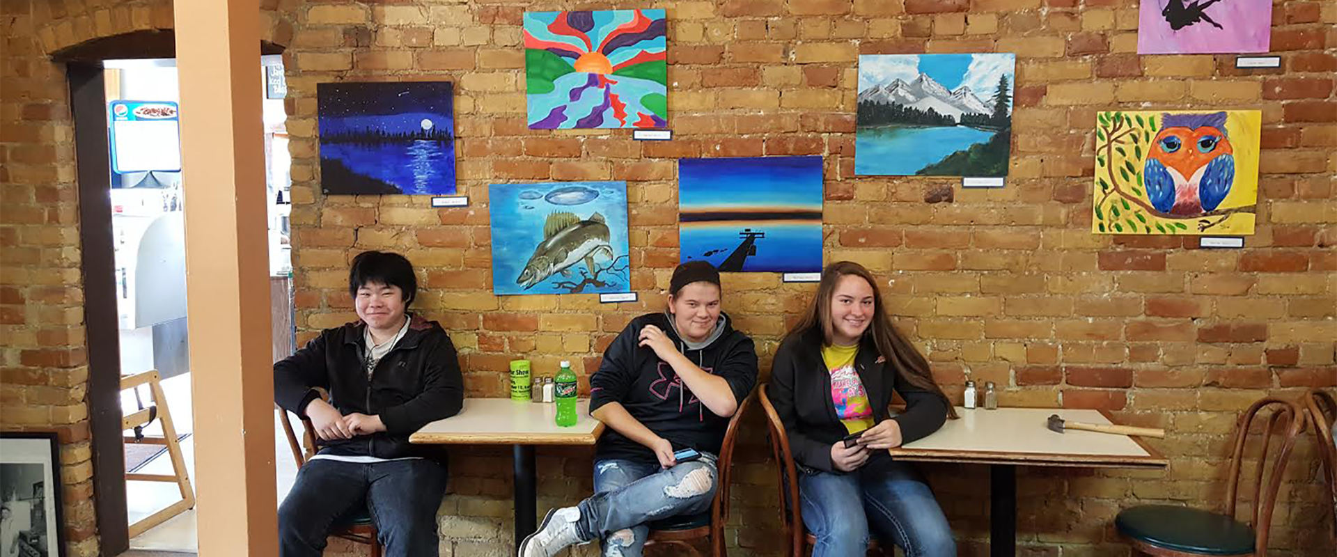 YME Art students displaying their artwork at Java River in Montevideo.